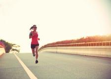 Woman runner running on city bridge road stock photos