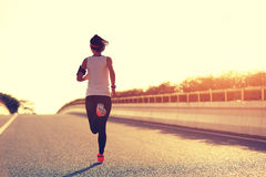 Woman runner running on city road Stock Photo