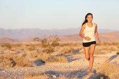 Woman runner running cross country trail run Stock Photos