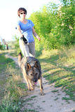 Woman runner running with dog on country road in summer nature Stock Photo
