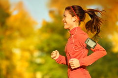Woman runner running in fall autumn forest. Listening to music on smartphone using earphones. Female fitness girl jogging on path in amazing fall foliage royalty free stock photos