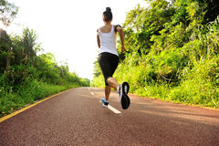 Woman runner running at forest trail Royalty Free Stock Photography
