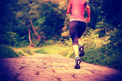 Woman runner running at forest trail Stock Photos