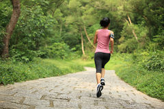 Woman runner running at forest trail Stock Photo