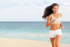 Woman runner running happy on beach. Laughing having fun while jogging and training for marathon run. Beautiful young mixed race Asian Caucasian female fitness Royalty Free Stock Image