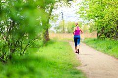 Woman runner running jogging in summer park stock images