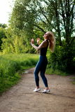 Woman runner running jogging in summer park, waving his hair stock image