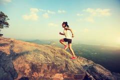 Woman runner running on mountain peak. Young asian woman runner running on mountain peak stock image