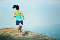 Woman runner running on mountain peak Royalty Free Stock Image