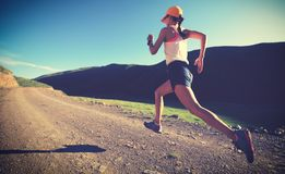 woman runner running on mountain trail stock photo