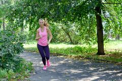 Woman runner running through the spring park road. Workout in a Park. Beautiful fit Girl. Fitness model outdoors. Stock Image