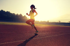Woman runner running on stadium track Royalty Free Stock Images