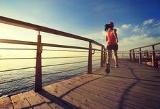 Woman runner running on sunrise seaside boardwalk. Young fitness woman runner running on sunrise seaside boardwalk Stock Photo