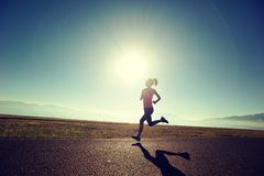 Woman runner running on sunrise seaside trail Royalty Free Stock Photo