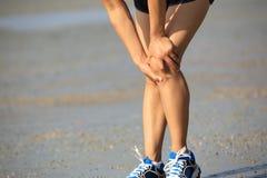 Woman runner sports injured knee Stock Photos