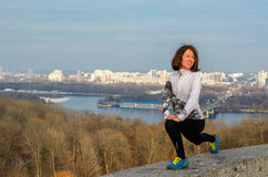 Woman runner stretching with beautiful city view Royalty Free Stock Image