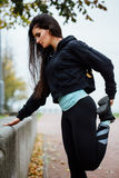 Woman runner stretching legs before run. royalty free stock photos