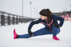 Woman runner stretching legs before run at snow winter promenade. Fitness concept. Royalty Free Stock Photos