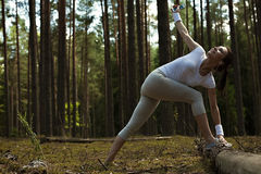 Woman runner stretching after running training in forest. Royalty Free Stock Images