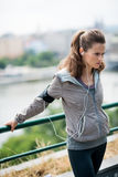 Woman runner stretching using a guardrail and listening to music. Feel that burn, and stretch those muscles... A woman is using a guardrail to stretch out her Royalty Free Stock Photos
