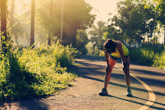 Woman runner take a break at morning tropical forest trail Stock Images