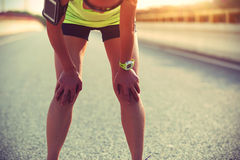 Woman runner taking a rest after running hard on city road Stock Images