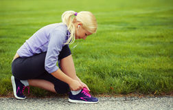 Woman runner tying running shoes. Blonde Girl over Grass stock photo