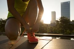 Woman runner tying shoelace royalty free stock photography