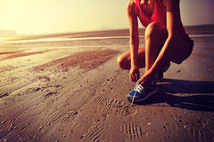 Woman runner tying shoelace before running on beach Stock Photos