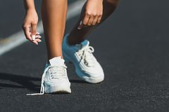 Woman runner tying shoelace on running track,Athlete to tie her shoes. Woman runner tying shoelace on running track. Athlete to tie her shoes royalty free stock photos