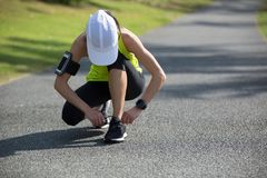 Woman runner tying shoelace at tropical park Stock Photo