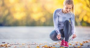 Free Woman Runner Tying Shoelaces Before Jogging In Autumn Tree Alley Park. Sports Female Autumn Outfit Leggings And Thermal Underwear Royalty Free Stock Images - 161150919