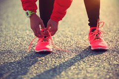 Woman runner tying shoelaces on city road Royalty Free Stock Images