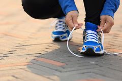 Woman runner tying shoelaces on city road Stock Image