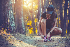 Woman Runner tying shoelaces on sneakers. Morning jogging in the forest. Fitness Stock Photo