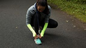 Woman runner tying the shoelaces. Woman runner in sport wear tying the shoelaces on asphalt road in the autumn park. Close-up super low motion shot with camera stock footage