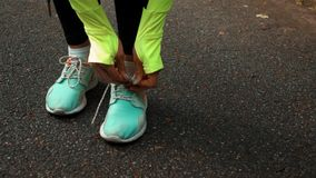 Woman runner tying the shoelaces. Woman runner in sport wear tying the shoelaces on asphalt road in the autumn park. Middle super slow motion shot with camera stock footage
