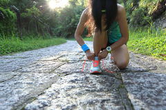 Woman runner tying shoelaces on stone trail. Young woman runner tying shoelaces on stone trail Royalty Free Stock Photo