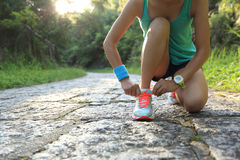 Woman runner tying shoelaces on stone trail. Young woman runner tying shoelaces on stone trail Royalty Free Stock Photos