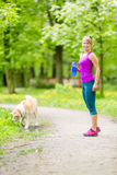 Woman runner walking with dog in summer park royalty free stock photography