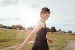 Woman runner walking on field in morning. Outdoor shot of smiling young woman runner looking at camera. Chinese female walking on field in morning Stock Image