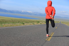 Woman runner warm up on country road Royalty Free Stock Photo
