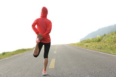 Woman runner warm up on country road Stock Photos