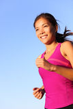 Woman running. Female runner jogging outdoors against blue sky. Beautiful healthy and fit young mixed race Caucasian / Chinese Asian fitness model jogging Stock Image