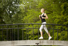 Woman running. A young woman running in the city park on a small bridge royalty free stock photography