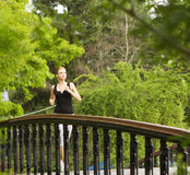 Woman running. A young woman running in the city park on a small bridge Stock Photo