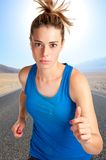 Woman Running. Young fit woman jogging,with a road behind and mountains Stock Image