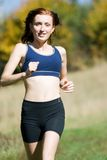 Woman and running. A youn woman is practising on a meadow Royalty Free Stock Images