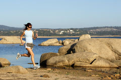 Woman Running. A woman running down a path at the beach Stock Image