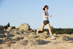 Woman Running. A woman running down a path at the beach Stock Photo